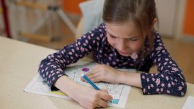 The girl paints the coloring with a felt-tip pen stock video footage