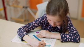 The girl paints the coloring with a felt-tip pen stock footage