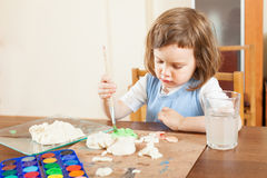 Girl paints dough figurines Royalty Free Stock Photography