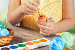 Girl paints Easter egg in orange color Royalty Free Stock Images