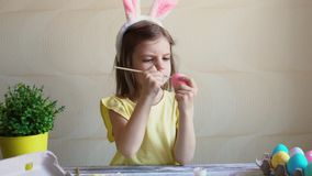 Girl paints the Easter eggs. Cheerful girl in rabbit costume paints the Easter eggs