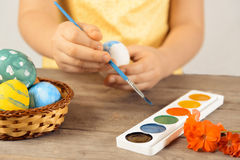 Girl paints egg for Easter day Royalty Free Stock Photography