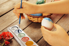 Girl paints egg for Easter holiday Stock Photography