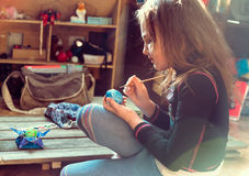 Girl paints egg for Easter indoors Royalty Free Stock Photography