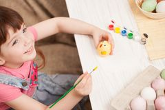 The girl paints the egg at the table at home. Classes with children in preparation for Easter. Children`s creativity. Copy space text Royalty Free Stock Photography