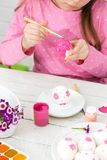 Girl paints eggs with a brush royalty free stock photography