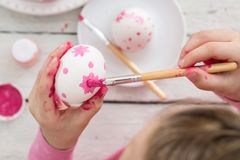 Girl paints eggs, top view royalty free stock photo