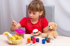Girl paints eggs Stock Image