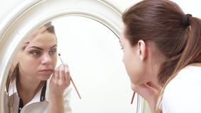 Girl paints face at mirror stock video