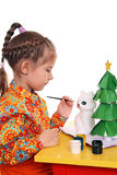 A girl paints the figure of a white cat. Out of papier-mache. Preparing for the New Year royalty free stock images