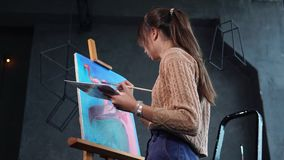 The girl paints flamingos in pink, the picture is on the easel in the studio. An adult girl dorisovyvaet flamingo oil paints, the picture is on the easel, next stock video