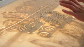 Girl paints on glass with sand stock video footage