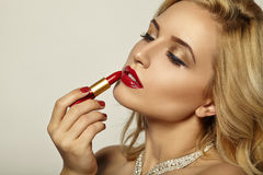 Girl Paints Her Lips Red Lipstick. Royalty Free Stock Photos