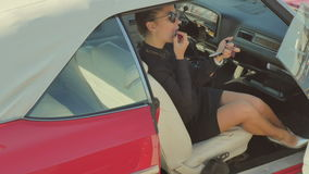 The girl paints her lips with red lipstick in a retro car. Beautiful woman in sunglasses sits on the passenger`s seat in a red retro car. Woman hold a small stock video footage
