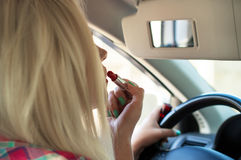 Girl paints her lips while sitting behind the wheel of a car Royalty Free Stock Images