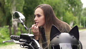 Girl paints her lips while sitting on motorcycle. stock video footage