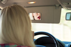 Girl paints her lips at the wheel the car stock images