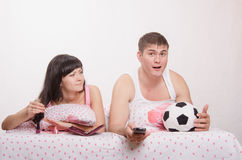 Girl paints her nails in bed, man emotionally watching soccer. Young girl and a guy in bed. Beautiful girl has a manicure, men watching soccer on TV Royalty Free Stock Image