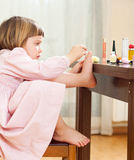 Girl paints her nails on  feet Stock Photography