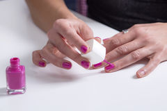 Girl paints her nails with pink nail polish Stock Photos