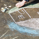Girl paints a house with colored chalk on asphalt Stock Image