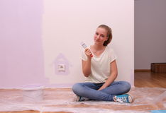 Girl paints house in purple color Royalty Free Stock Images