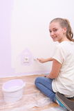 Girl paints house in purple color Royalty Free Stock Image