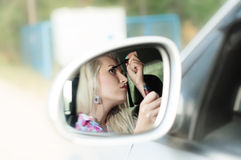 Girl paints the lashes for driving the car Stock Photo