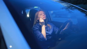 The girl paints lips with a lip gloss, sitting at the wheel of a car. The girl paints lips with a lip gloss, lipstick while sitting at the wheel of a car stock video footage