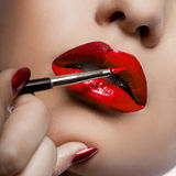 Girl paints lips with lipstick Royalty Free Stock Images