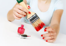 Girl paints nails with the big brush. Royalty Free Stock Photography