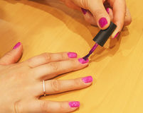 The girl paints nails with varnish royalty free stock photo