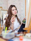 Girl paints with oil colors and brushes Stock Photography