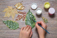 Girl paints patterns of dry autumn leaves Royalty Free Stock Photography