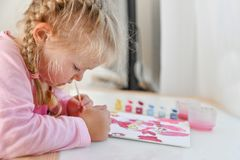 The girl paints the picture with her left hand in color paints royalty free stock photos