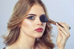 The Girl paints powder on the face, completes the smokey eyes make-up in the beauty salon. stock images
