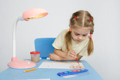 Girl paints sitting at the table Stock Photos