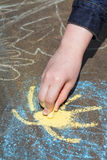 Girl paints sun in blue sky with chalks outdoors Royalty Free Stock Photo