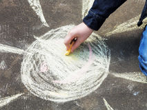 Girl paints a sun with colored chalk on asphalt Royalty Free Stock Images
