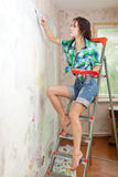 Girl paints wall with brush Royalty Free Stock Photos