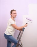 Girl paints wall in lilac color with roller Royalty Free Stock Photography