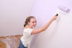Girl paints wall in lilac color with roller Royalty Free Stock Image