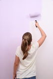 Girl paints wall in lilac color with roller Royalty Free Stock Images