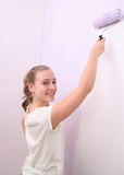 Girl paints wall in lilac color with roller Royalty Free Stock Photo