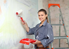 Girl paints wall with roller Royalty Free Stock Images