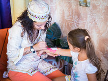 Girl paints a washable tattoo on the arm of a child. Stock Image