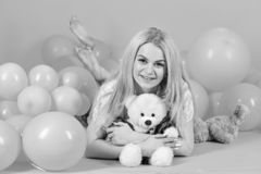 Girl in pajama, domestic clothes lay near air balloons, pink background. Blonde on smiling face relaxing with teddy bear