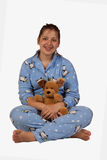 Girl in pajamas. Smiling hispanic teenage girl sitting crosssed legged wearing pajamas and holding a toy stuffed animal Stock Image