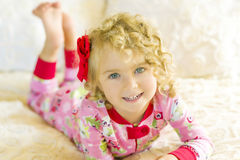 Girl in  Pajamas On Bed. A toddler with blond curly hair and big blue eyes, wearing red, pink and green Christmas pajamas lays out on the bed with her feet Royalty Free Stock Image