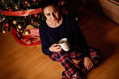 Girl drinking beverage in front of christmas tree royalty free stock photos